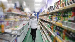 Shelves with products and buyers go to the supermarket Stock Footage
