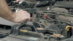 Auto mechanic visually examines car motor engine Stock Footage