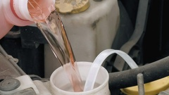 Pouring pink windshield washer fluid into the car Stock Footage