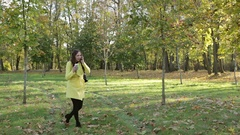 Young woman in a yellow coat walking in the park and talking on the phone. Stock Footage