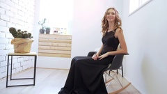 Fashion video of young beautiful woman in black long dress sitting in armchair Arkistovideo
