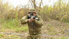 4K.Moving Soldier with automatic rifle  in autumn wood. Stabilized shot  Stock Footage