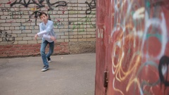 Teen boy dancing, street dancing on the background of brick wall Stock Footage
