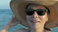 A female in sunglasses putting on her fedora hat Stock Footage