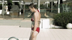 A lady in red bikini walks out of the pool Stock Footage