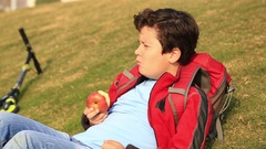 Portrait of a  young boy eating red apple at the outdoor 2 Stock Footage