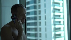 Young, topless man talking on cellphone standing by window at home Stock Footage