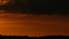 Sun leaves because of clouds and is slowly rolled up for trees on the horizon. Stock Footage