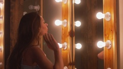 Young attractive Caucasian female checking her make up in dressing room mirror Stock Footage