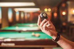 Male hand shows a billiard sphere number eight. Stock Photos