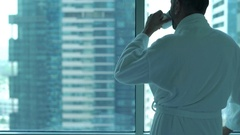 Young man in bathrobe drinking coffee and admire view form window at home Stock Footage