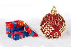 Red x-mas ball on snow with presents isolated white Kuvituskuvat