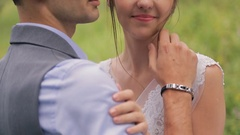 Happy groom tenderly embraces and kisses beautiful bride, close up Stock Footage