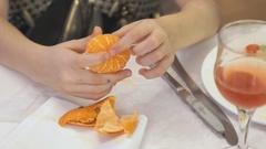 Woman peeling a mandarine indoors Stock Footage