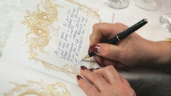 Woman writing greeting in the book of greetings Stock Footage