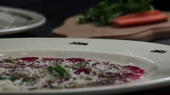 Serving carpaccio meat dish green herbs rucola slow motion сlose up HD video Stock Footage