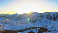 Aerial winter mountain sunset afternoon beautiful horizon snow sun sunlight sky Stock Footage