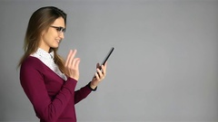 Beautiful young woman in glasses and business casual style using tablet Stock Footage