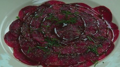 Serving carpaccio meat dish with parmesan cheese slow motion сlose up HD video Stock Footage