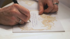Female hand writing greeting text in book.Close up Stock Footage