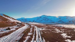 Aerial winter landscape snow path trail mountains hilly horizon sunny blue sky Stock Footage