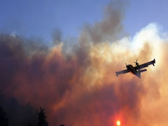 Amphibian airplane drops fire retardant on a forest fire near gas station Stock Footage