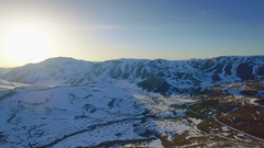 Winter mountain sunrise horizon aerial rotating motion grass snow skyline sun Stock Footage