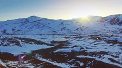 Winter mountain water pond aerial forward motion frozen lake grass snow sunlight Stock Footage