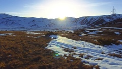 Aerial forward motion winter mountain scenery low grass snow sun light skyline Stock Footage