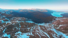 Aerial wide winter landscape snow mountain peaks horizon lake sunny blue sky Stock Footage