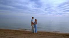 Pregnant couple beach. Pregnant couple hugging on sea beach. Love couple beach Stock Footage