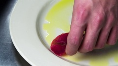 Chef serves carpaccio dish 4k сlose up video. Hand puts raw meat slice on plate Stock Footage