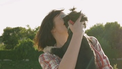Woman holding dog in hands with backlight sunset Stock Footage