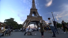 Eiffel Tower tourists walk past street sellers, replica merchandise Stock Footage