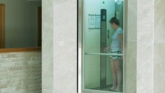 A female is standing in glass moving lift Stock Footage