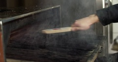 Cleaning grill grid in barbecue charcoal oven 4k video. Brush scrubs restaurant Stock Footage