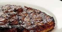 Served grilled meat steak on plate 4k rotation close-up video. Fried beef Stock Footage