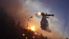 Amphibian airplane drops fire retardant on a forest near gas station. Stock Footage