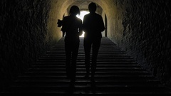 Silhouette of women going away in a dark tunnel Stock Footage