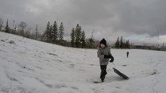 Boy running up hill with sled Stock Footage