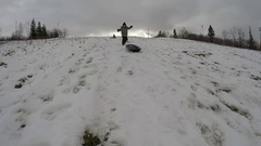Boy Tobogganing down snowy hill in slow motion Stock Footage