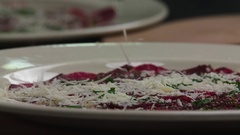 Serving carpaccio meat parmesan cheese slow motion сlose up HD restaurant video Stock Footage