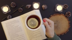 Top view woman read the book on the table with tea and candles Stock Footage