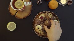 Top view man takes cookies from the table with tea and candles hands from above. Stock Footage