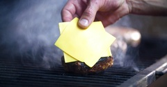 Chef prepares cheeseburger: grilling meat patty with cheese for burger 4k video Stock Footage