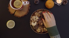 Top view woman takes cookies from the table with tea and candles . Stock Footage