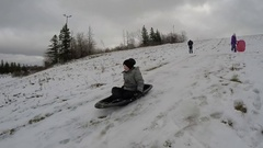 Brother and sister - Boy tobogganing on snow sled hill Stock Footage