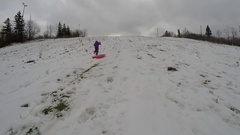 Brother and sister racing up the sled hill Stock Footage