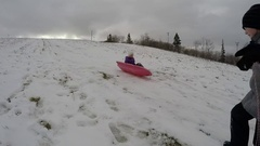 Brother and sister tobogganing in the winter Stock Footage