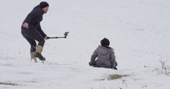 Dad filming son sledding down hill Stock Footage